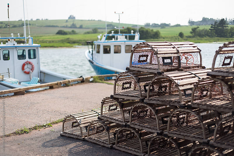 Rows of empty lobster pots on seaside dock with boats in background by Matthew Spaulding for Stocksy United