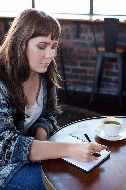 Woman working from a cafe writing in her journal by Daxiao Productions for Stocksy United