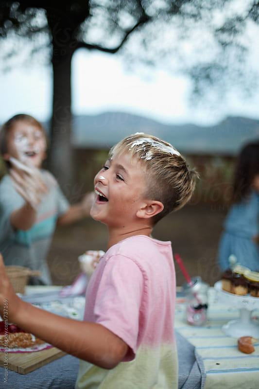 Happy kids playing with birthday cake by Miquel Llonch for Stocksy United