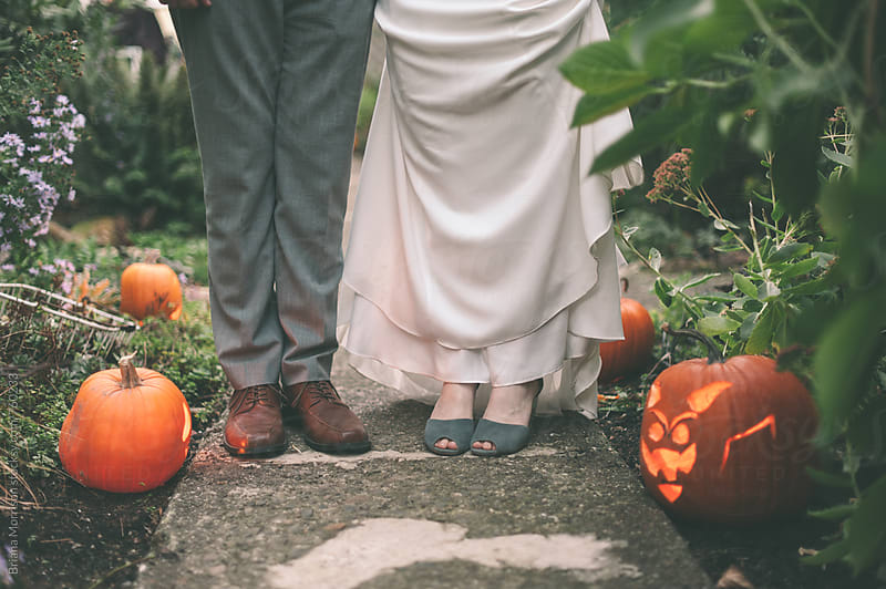 Feet of the Bride and Groom among Jack-O-Lanterns in Autumn by Briana Morrison for Stocksy United