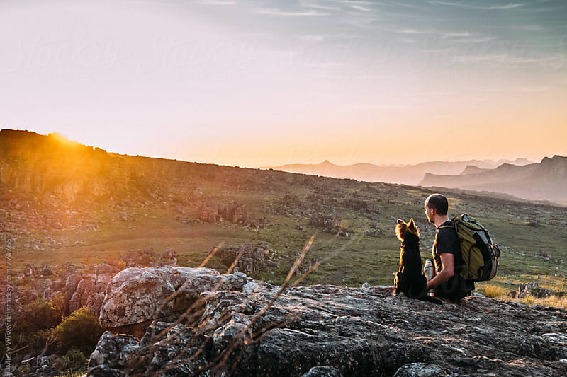Hiker with his dog taking a break and watching the sunset in a mountainous valley by Micky Wiswedel for Stocksy United