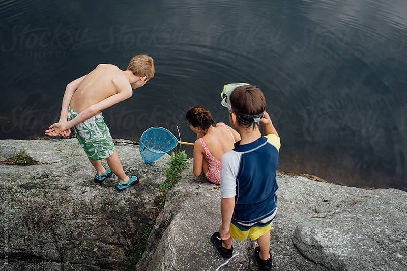 kids looking at  fishing net by Léa Jones for Stocksy United