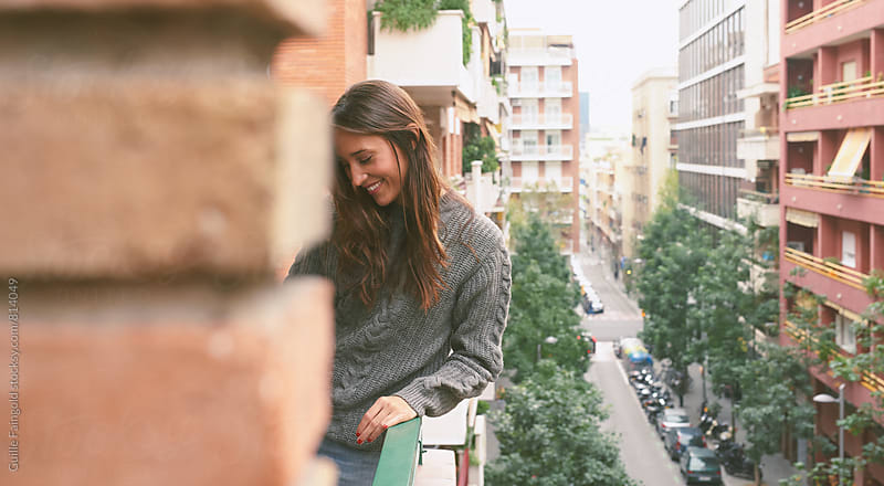 Smiling woman standing on balcony.Beautiful view on urban street by Guille Faingold for Stocksy United