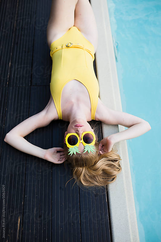 Young woman wearing yellow bikini sitting by the pool by Jovana Rikalo for Stocksy United