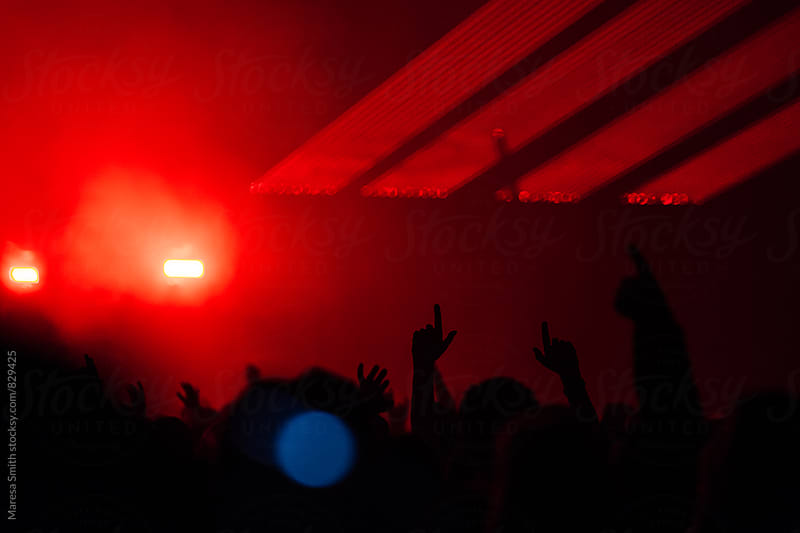 Silhouetted hands in the air at a gig, lit up with red lights by Maresa Smith for Stocksy United