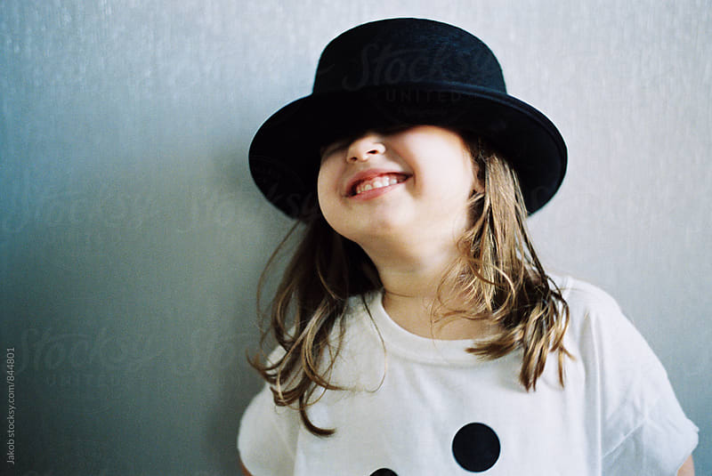 Beautiful young girl in an over sized t shirt playing with a hat by Jakob for Stocksy United