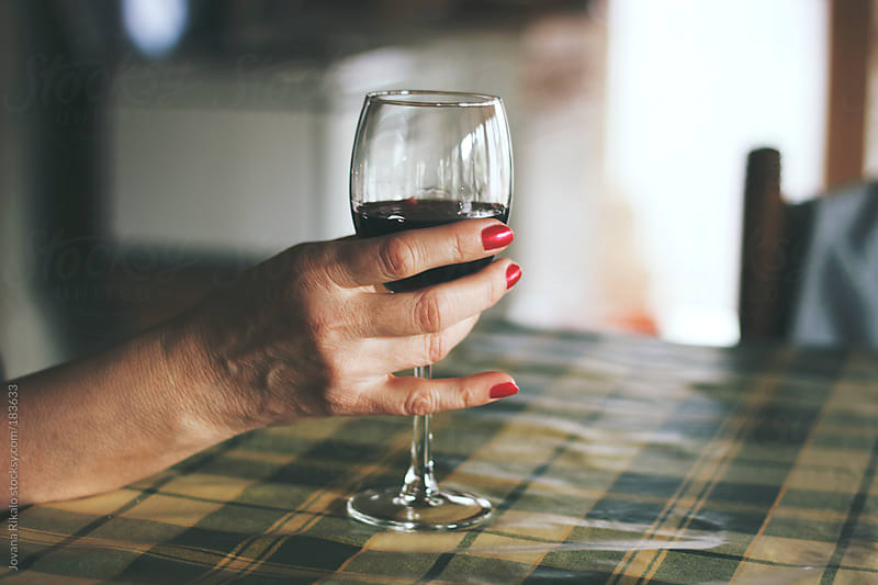 Woman holding glass of wine by Jovana Rikalo for Stocksy United