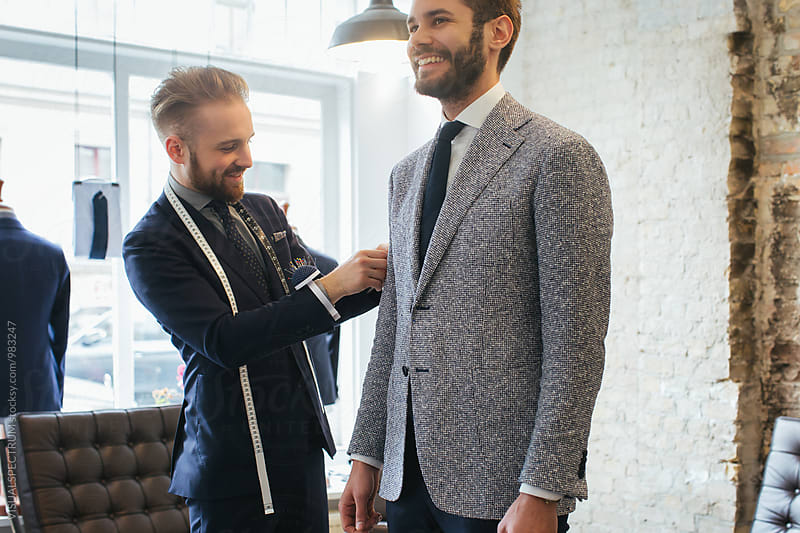 Men's Fashion - Young Caucasian Tailor Adjusting Suit of Young Smiling Caucasian Customer by Julien L. Balmer for Stocksy United