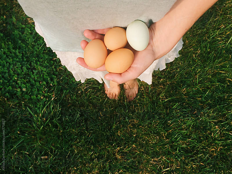 A woman holds four farm fresh eggs. by Kelsey Gerhard for Stocksy United