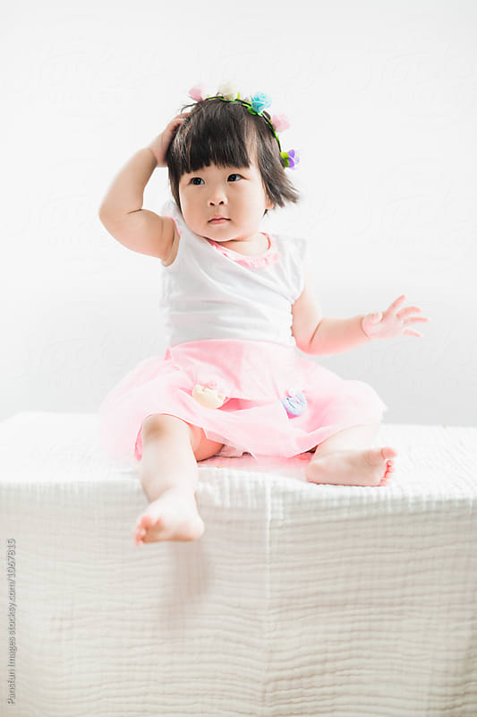 baby girl sitting by Pansfun Images for Stocksy United