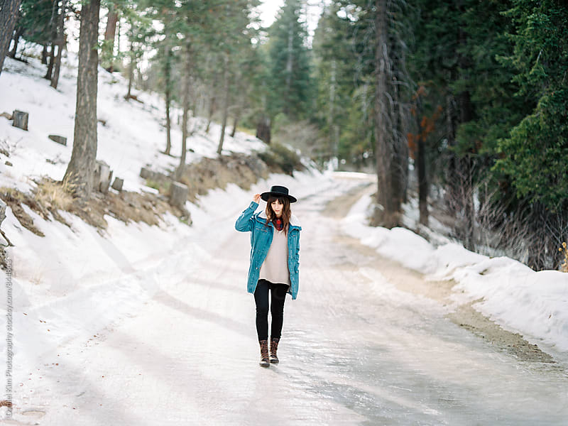 Young woman walking on icy road by Daniel Kim Photography for Stocksy United