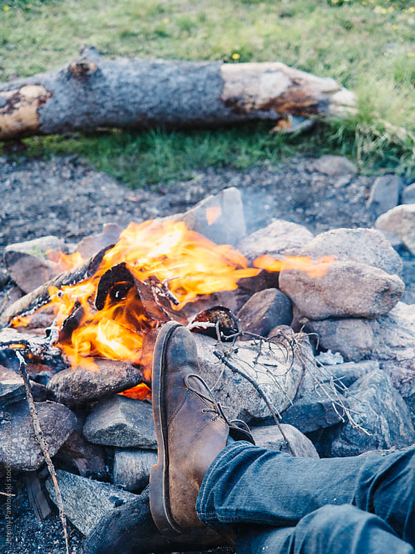 Mens feet  by camp fire. In boots and jeans by Jeremy Pawlowski for Stocksy United