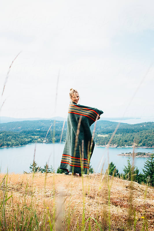 Happy Young Blonde Woman Wrapped In Wool Blanket Standing On Forest Island Hillside by Luke Mattson for Stocksy United