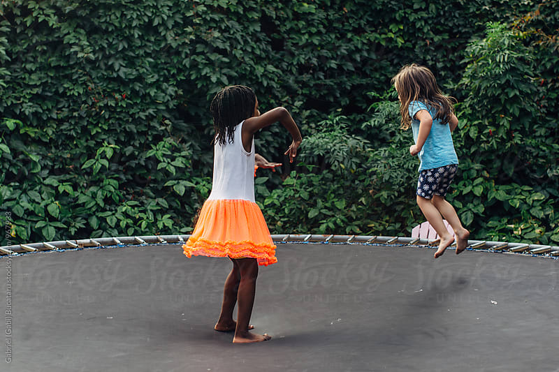Black and Caucasian girls on trampoline by Gabriel (Gabi) Bucataru for Stocksy United