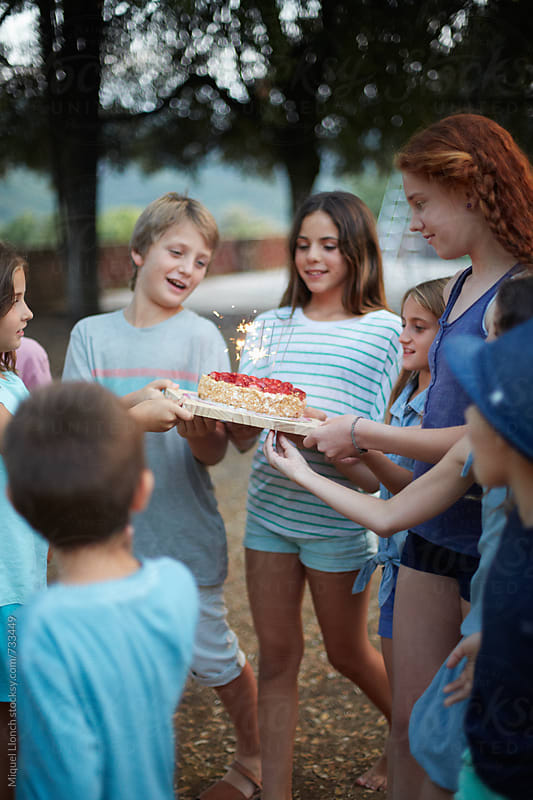 Group of happy children carrying a birthday cake by Miquel Llonch for Stocksy United