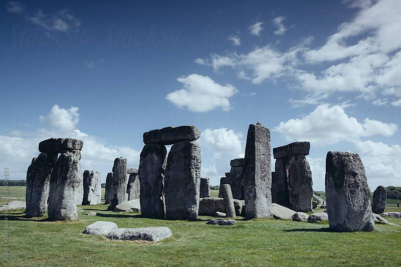 Stonehenge historic site on green grass under blue sky by Robert Kohlhuber for Stocksy United