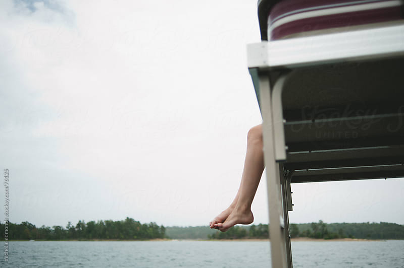 Girl's feet hanging off of boat in summer by michelle edmonds for Stocksy United