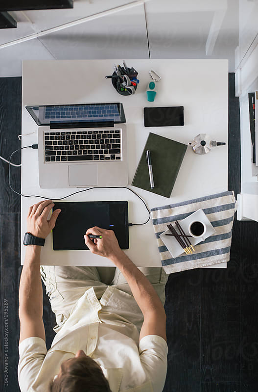 Designer - man working from home on his laptop by Jovo Jovanovic for Stocksy United