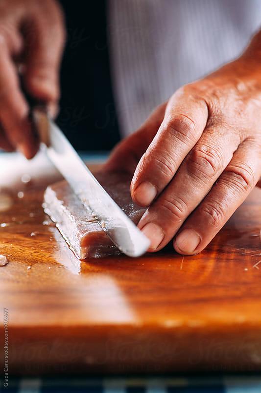 Man cutting tuna by Giada Canu for Stocksy United