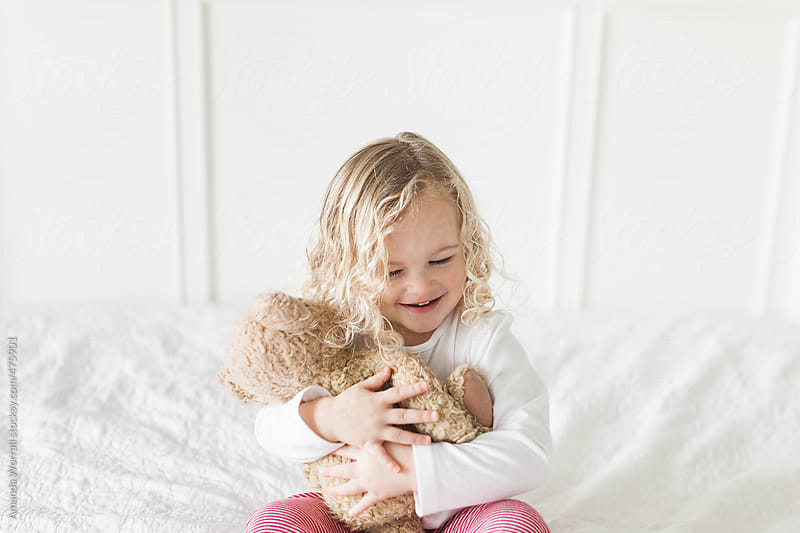 Happy young girl wearing red and white striped pajamas hugs teddy bear by Amanda Worrall for Stocksy United