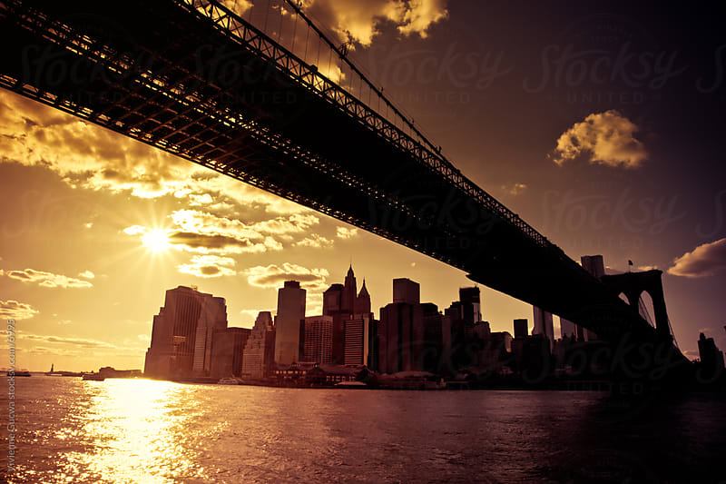 The New York City Skyline at Sunset From  Under the Brooklyn Bridge by Vivienne Gucwa for Stocksy United