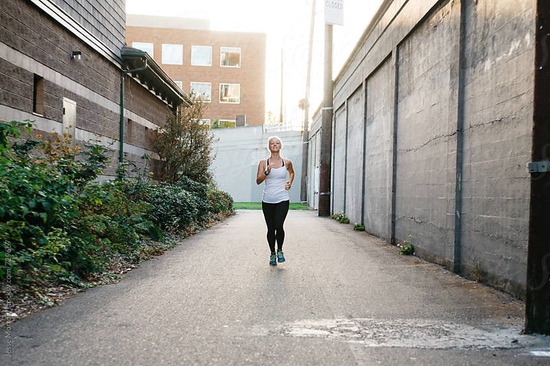 young woman running in fitness clothing through urban city environment by Jesse Morrow for Stocksy United