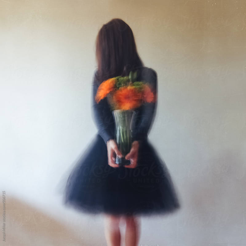 Slightly blurred image of woman, with face hidden, holding a vase filled with bright orange flowers by Jacqui Miller for Stocksy United