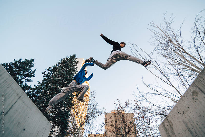 Two men jumping during a parkour training at sunset by Inuk Studio for Stocksy United