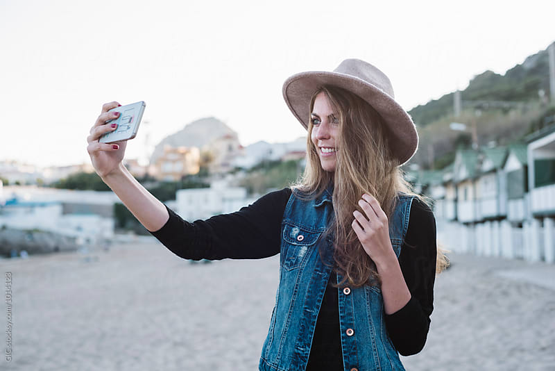 Beautiful woman taking a self portrait with the phone by Simone Becchetti for Stocksy United