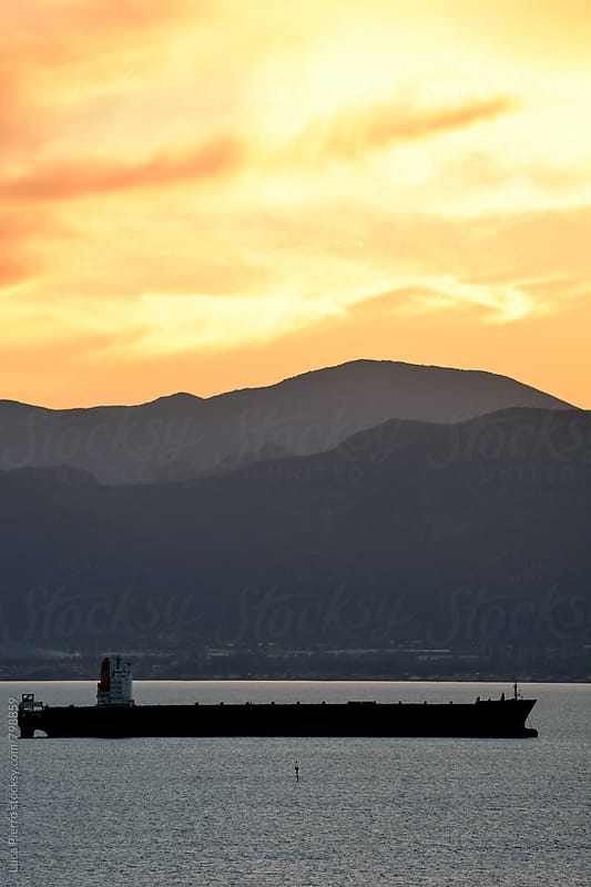 Oil tanker ship at sunset in the sea by Luca Pierro for Stocksy United