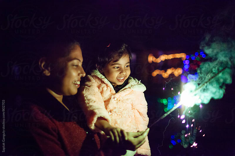 Mother and daughter having fun with smoky sparkler by Saptak Ganguly for Stocksy United