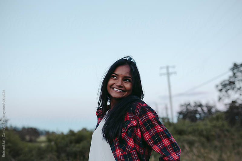 Portraits of young south asian girl enjoying being outside by Rob and Julia Campbell for Stocksy United