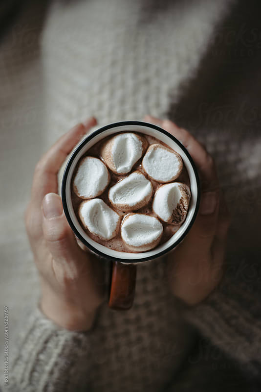 Woman holding hot cocoa by Pixel Stories for Stocksy United