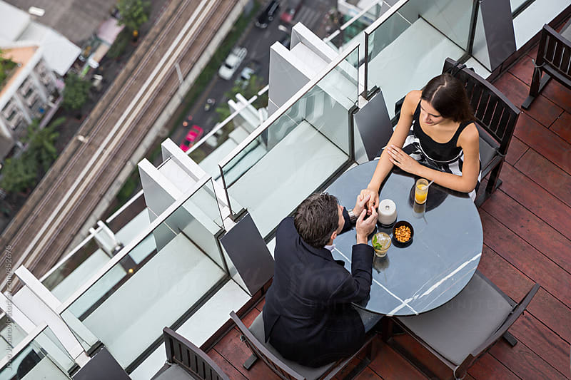 Aerial view of a couple in love on a date in a modern rooftop restaurant  by Jovo Jovanovic for Stocksy United