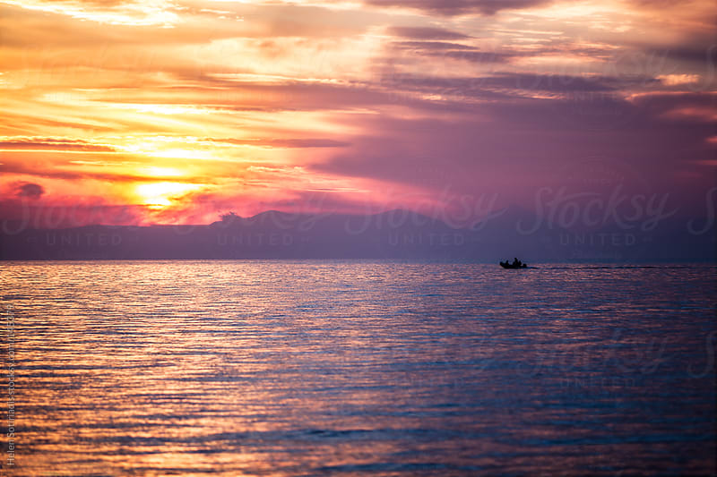 Motorboat Speeds Through a Sunset by Helen Sotiriadis for Stocksy United