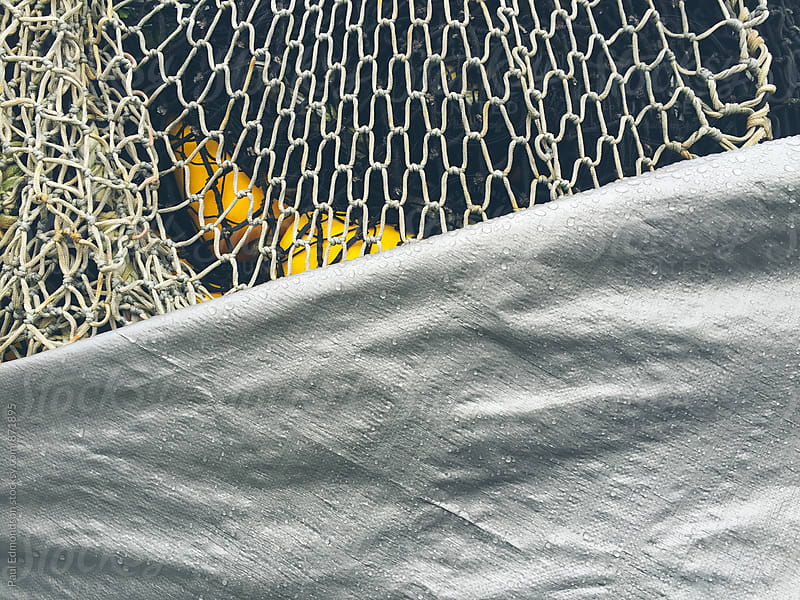 Close up of commercial fishing nets and tarp by Paul Edmondson for Stocksy United