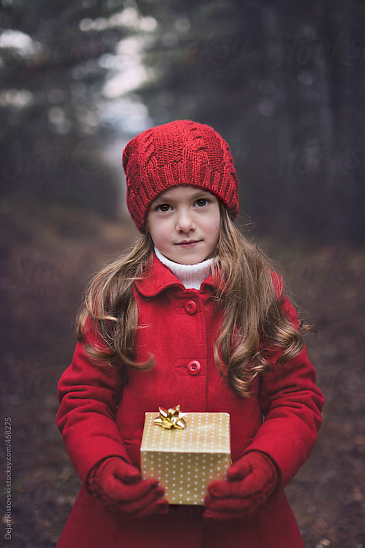 Child holding Christmas gift by Dejan Ristovski for Stocksy United