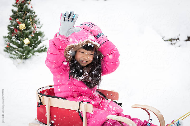 little girl riding sled on snow by jira Saki for Stocksy United