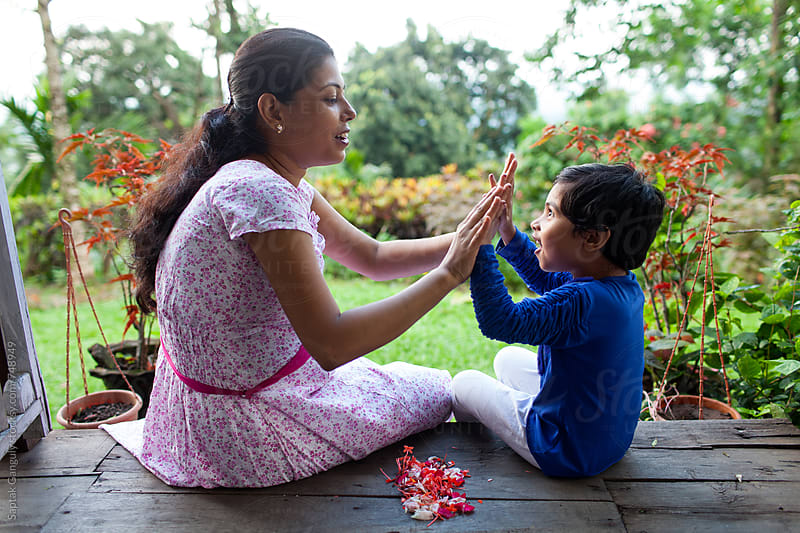 Happy mother giving high five to her little daughter sitting in the porch by Saptak Ganguly for Stocksy United