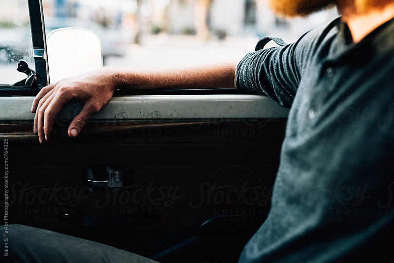 Young man sitting in an old car by Isaiah & Taylor Photography for Stocksy United