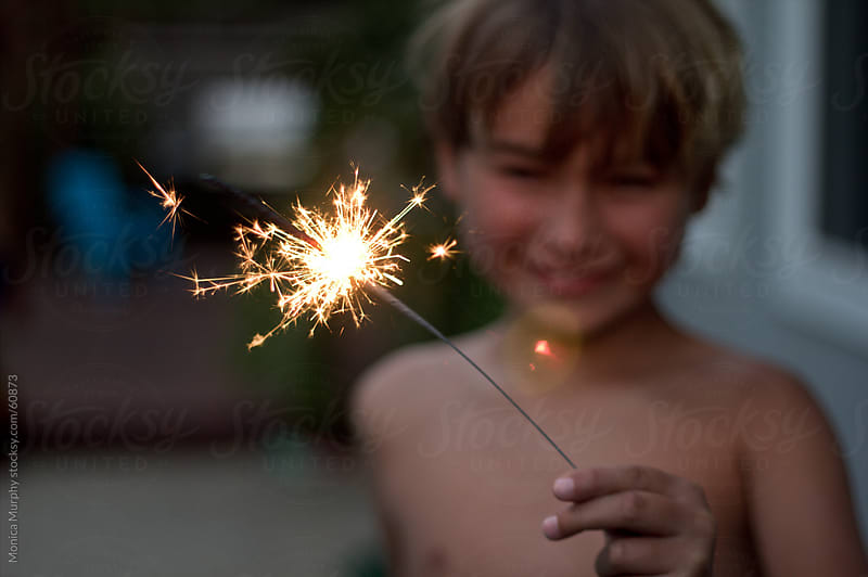 Young boy holding a lit sparkler smiling on the 4th of July by Monica Murphy for Stocksy United