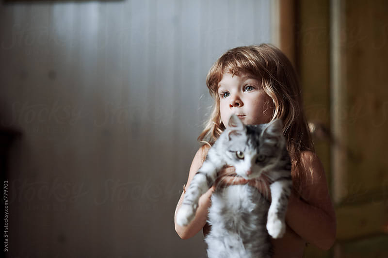 Little girl and her tabby kitten by Svetlana Shchemeleva for Stocksy United