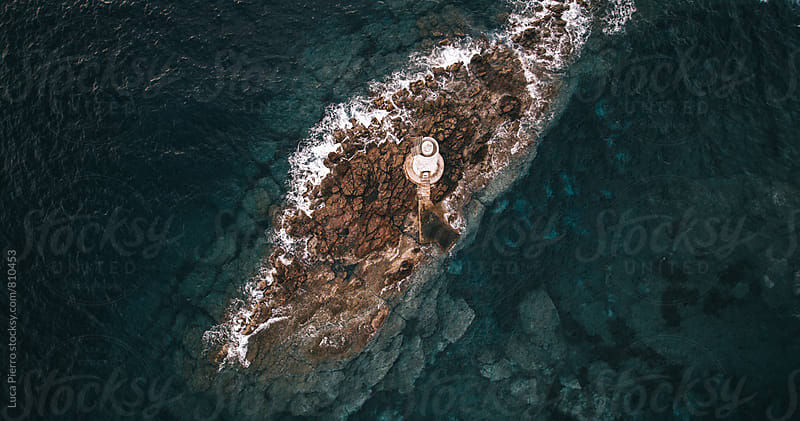 Aerial view of a lighthouse on a rock in the meddle of the sea by Luca Pierro for Stocksy United