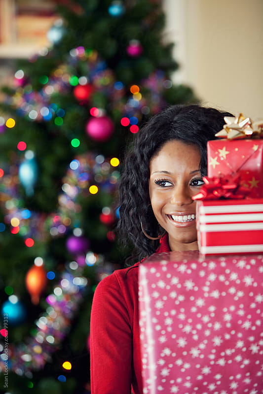 Christmas: Woman Behind Stack of Wrapped Gifts by Sean Locke for Stocksy United