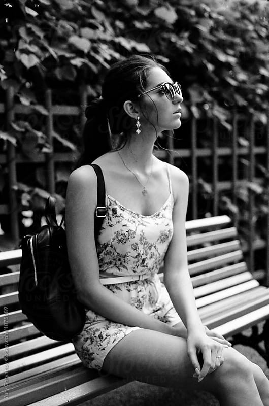 Portrait of a young woman on a bench by Yury Goryanoy for Stocksy United