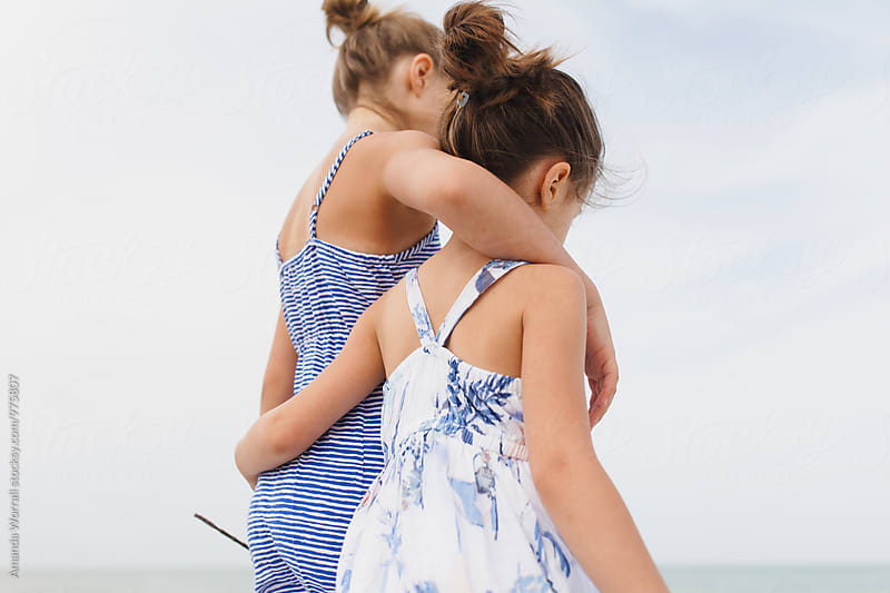 Two girls walking with arms around each other on the beach by Amanda Worrall for Stocksy United
