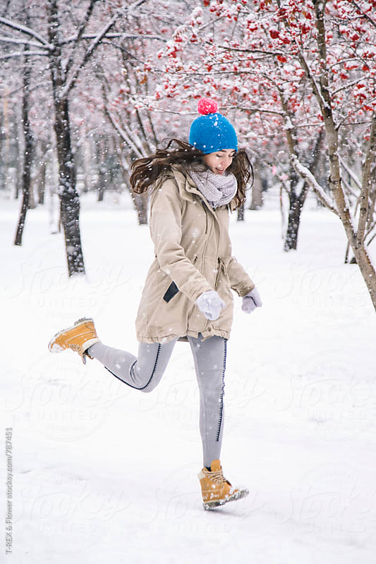 Pretty young woman running in winter park by Danil Nevsky for Stocksy United