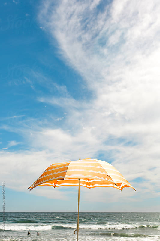Orange beach umbrella against a cloudy blue sky by Amy Covington for Stocksy United