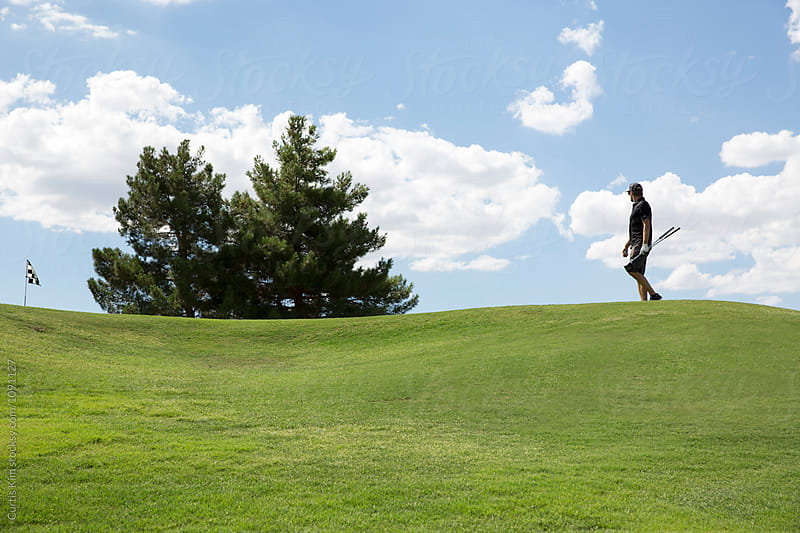 Man walking to putt on a golf course by Curtis Kim for Stocksy United