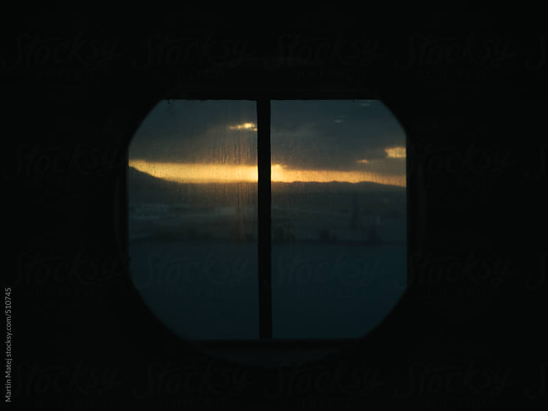 Sunset framed in window on boat by Martin Matej for Stocksy United